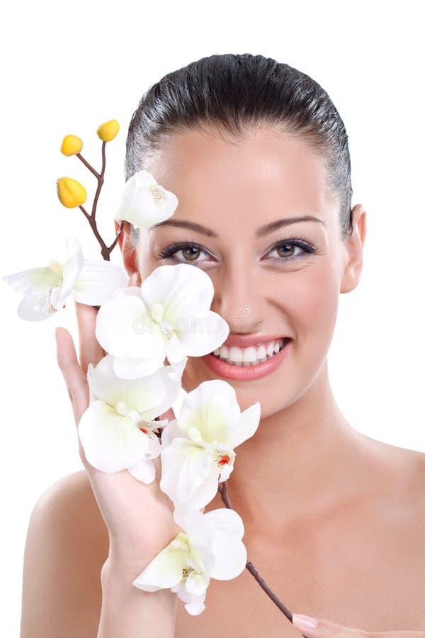 Framsida av en härlig ung kvinna med blomman royaltyfri fotografi