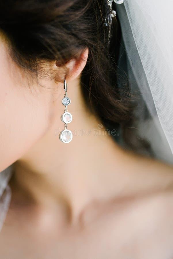 Framsida av en ung kvinna med stora örhängen tätt upp fotografering för bildbyråer