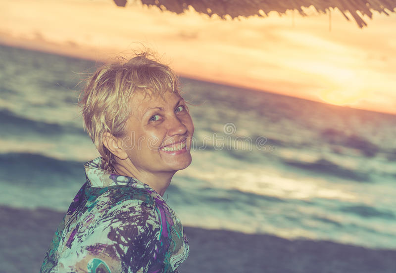 Framsida av härligt kvinnasammanträde på en strand royaltyfri foto