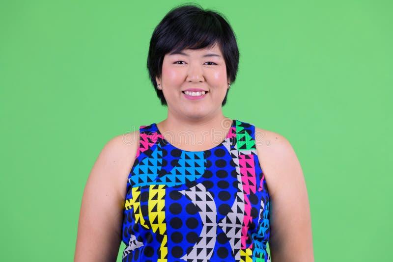 Framsida av ungt lyckligt överviktigt asiatiskt le för kvinna som är klart att festa arkivfoto