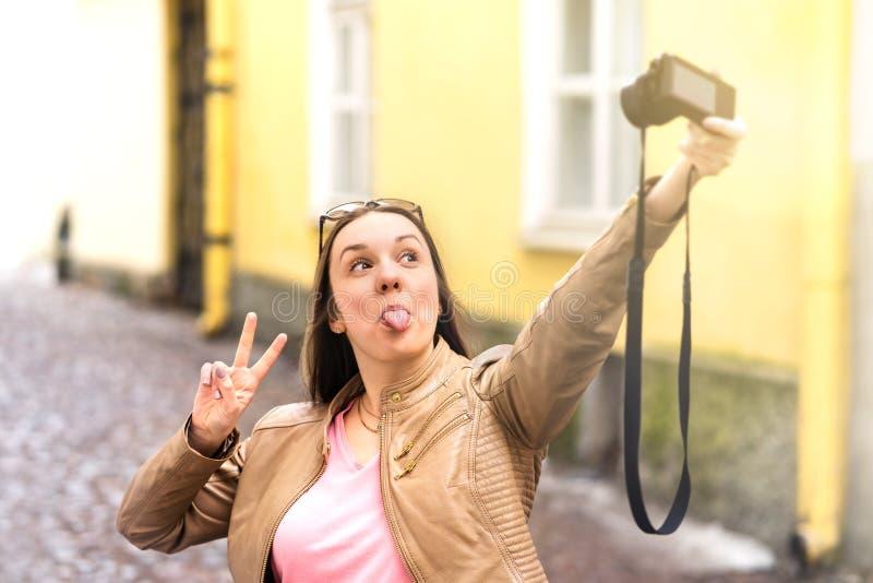Framsida för danande för ung kvinna enfaldig och visningtunga till kameran royaltyfri fotografi