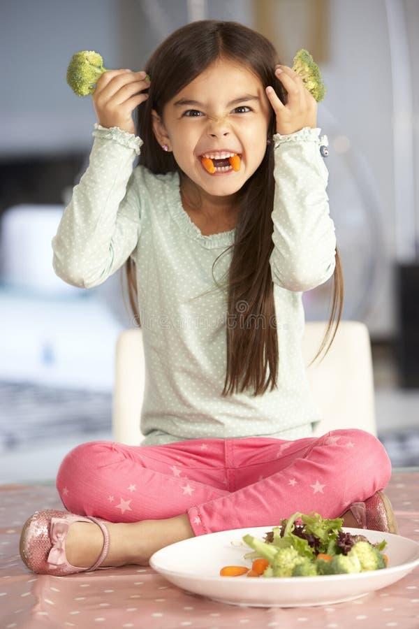 Framsida för flickadanandejäkel med plattan av nya grönsaker arkivbilder
