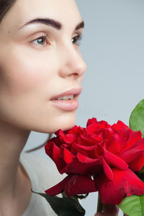 Framsida för kvinna för skönhetmodemodell Stående med röda rosblommor perfekt hud arkivfoto