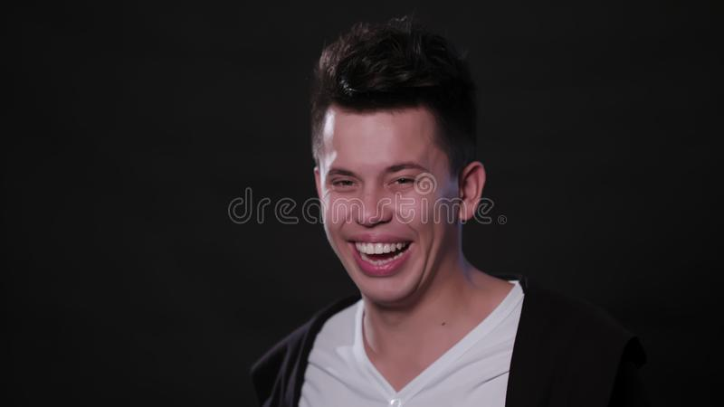 Framsida för man` som s ler mot en svart bakgrund arkivfoton