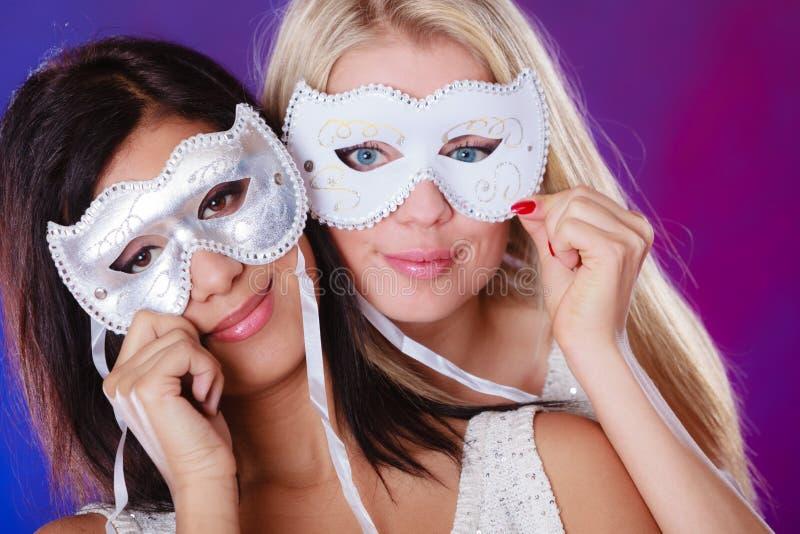 Framsida för två kvinnor med venetian maskeringar för karneval royaltyfri foto