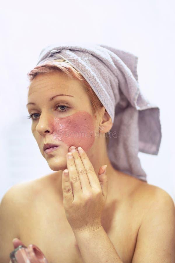 Framsida som skalar maskeringen, skönhetbehandling, skincare Kvinna som får ansikts- omsorg royaltyfria bilder
