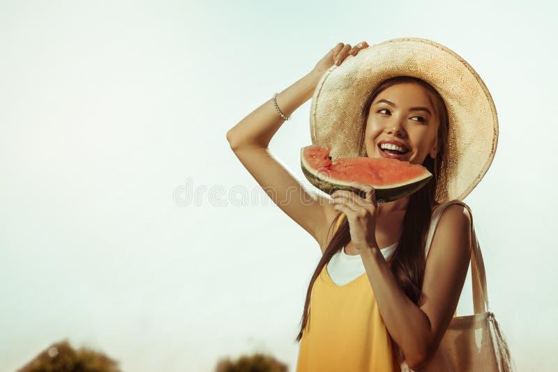 Framsida-stående av att blända den härliga le älskvärda damen som äter vattenmelon royaltyfria bilder