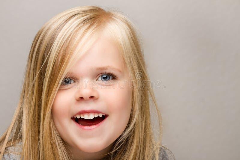 framsidaflicka henne enormt leendebarn royaltyfri fotografi