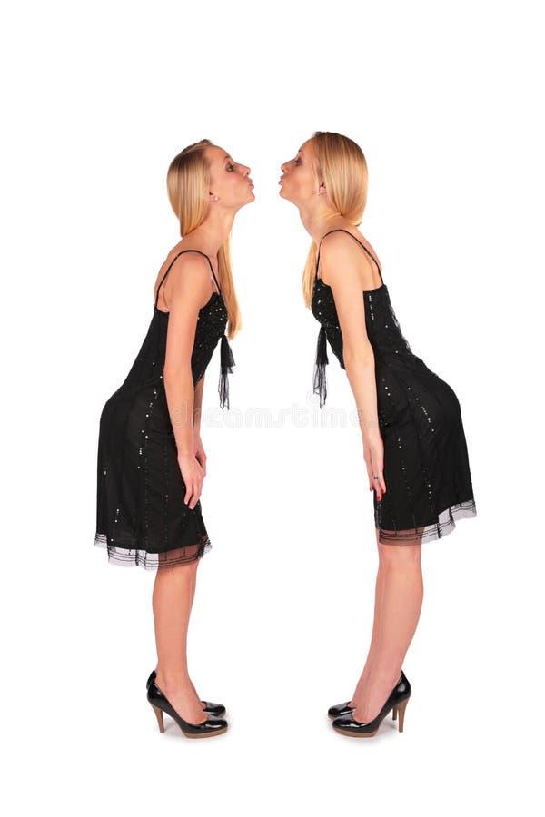 framsidaflickor som kysser stands för att koppla samman royaltyfria bilder