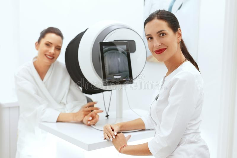 Framsidahud analyserar CosmetologistAnalyzing Woman Facial hud royaltyfria bilder