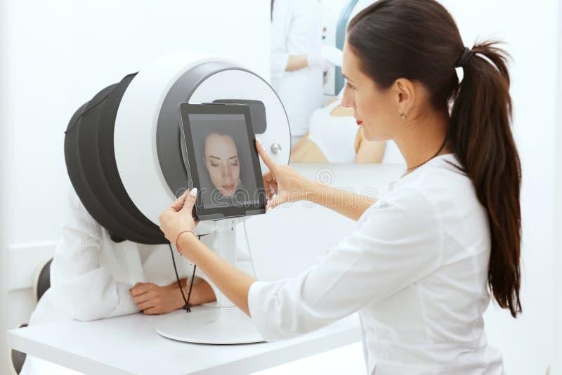 Framsidahudanalys Kvinna på Cosmetology som gör huddiagnostik arkivfoton