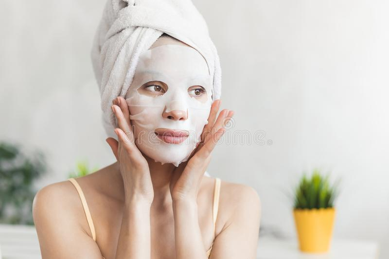 Framsidahudomsorg Attraktiv ung kvinna som slås in i badlakan, med den vita fuktaframsidamaskeringen Begrepp för hudomsorg royaltyfri foto