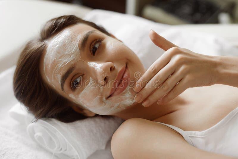 Framsidahudomsorg Härlig kvinna med den ansikts- kosmetiska maskeringen på Spa royaltyfri bild