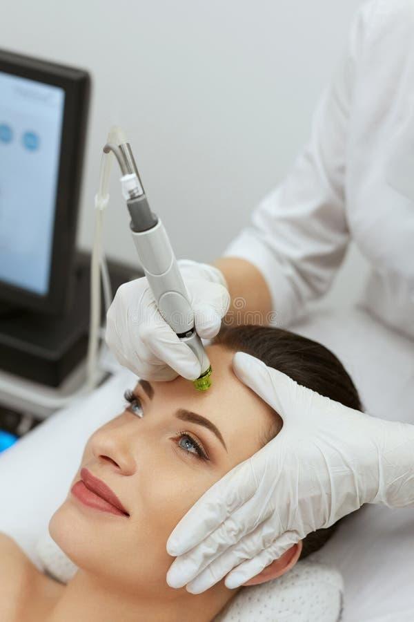 Framsidahudomsorg Kvinna som får Exfoliating behandling för ansikts- Hydro arkivbilder