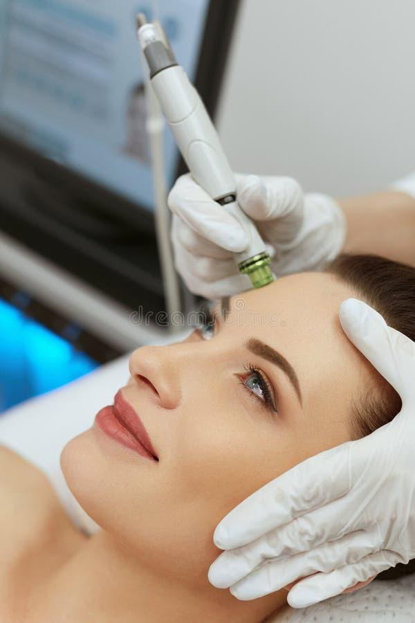 Framsidahudomsorg Kvinna som får Exfoliating behandling för ansikts- Hydro arkivbild