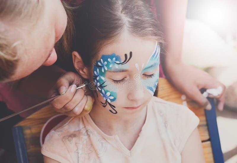 Framsidamålning för kvinnligt barn, danandefjärilsprocess royaltyfria bilder
