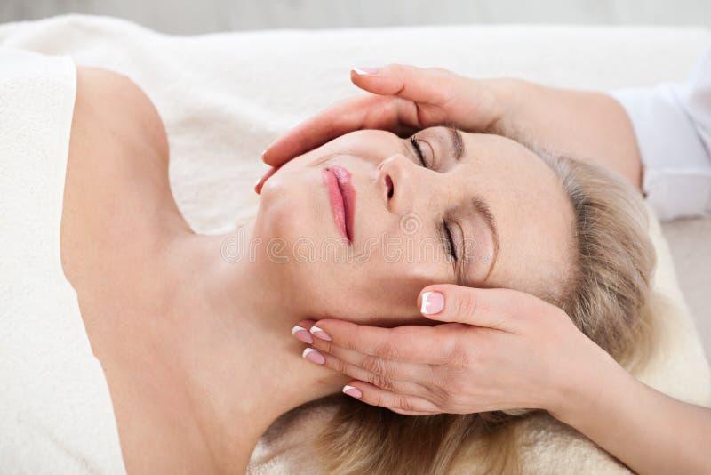 Framsidamassage i brunnsortmakro Attraktiv kvinna med nära ögon som tar hudomsorg Selektiv fokus för massageframsida royaltyfri bild
