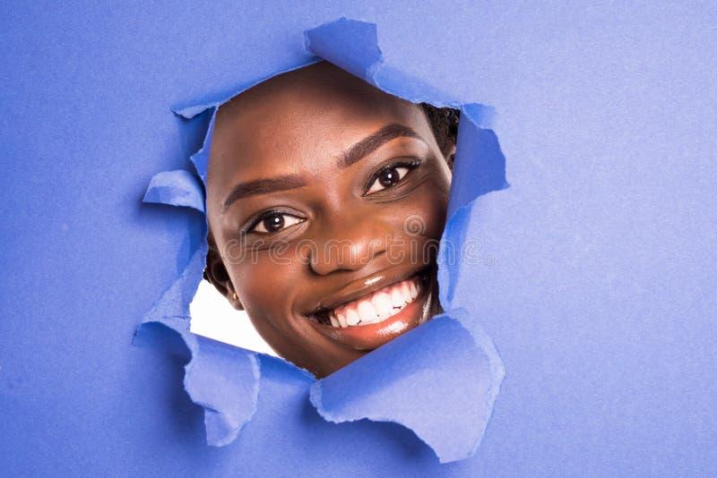 Framsidan av en ung härlig afrikansk flicka med ett ljust smink och pösiga purpurfärgade kantjämliken in i ett hål i violett papp royaltyfria foton