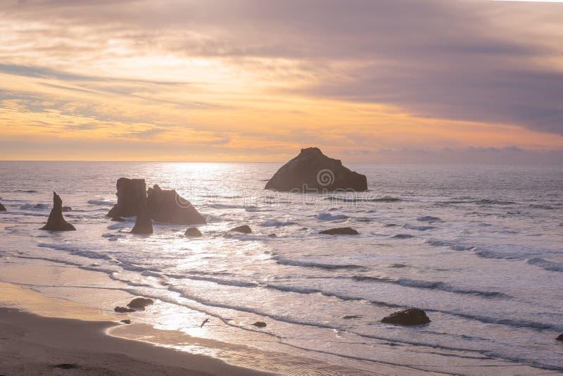 Framsidan vaggar på den Oregon kusten på solnedgången arkivfoton