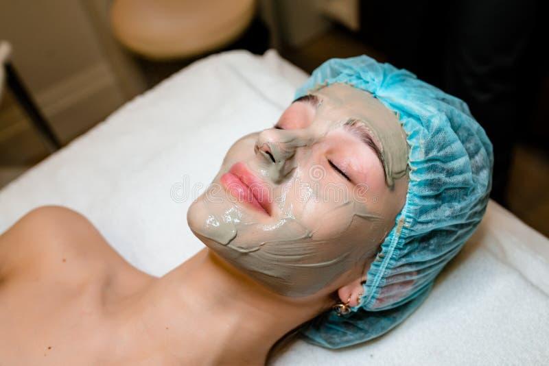 Framsidaskalningsmaskering, brunnsortskönhetbehandling, skincare Kvinna som får ansikts- omsorg av kosmetologen på brunnsortsalon royaltyfria bilder