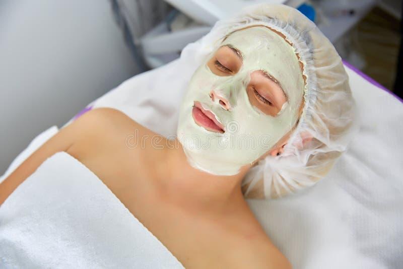 Framsidaskalningsmaskering, brunnsortskönhetbehandling, skincare Kvinna som får ansikts- omsorg av kosmetologen på brunnsortsalon arkivfoto