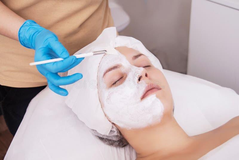 Framsidaskalningsmaskering, brunnsortsk?nhetbehandling, skincare Kvinna som f?r ansikts- omsorg av kosmetologen p? brunnsortsalon arkivfoto