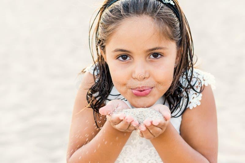 Framsidaskott av flickan som blåser sand arkivfoto