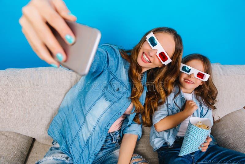 Framställning av den lyckliga selfieståenden av den nätta unga modern med den glade dottern som ler till kameran på soffan på blå arkivfoton