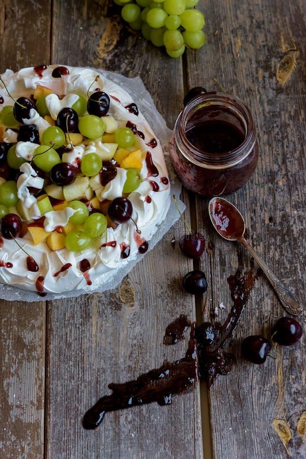 Framställning av en Pavlova efterrätt med frukt och driftstopp royaltyfri fotografi