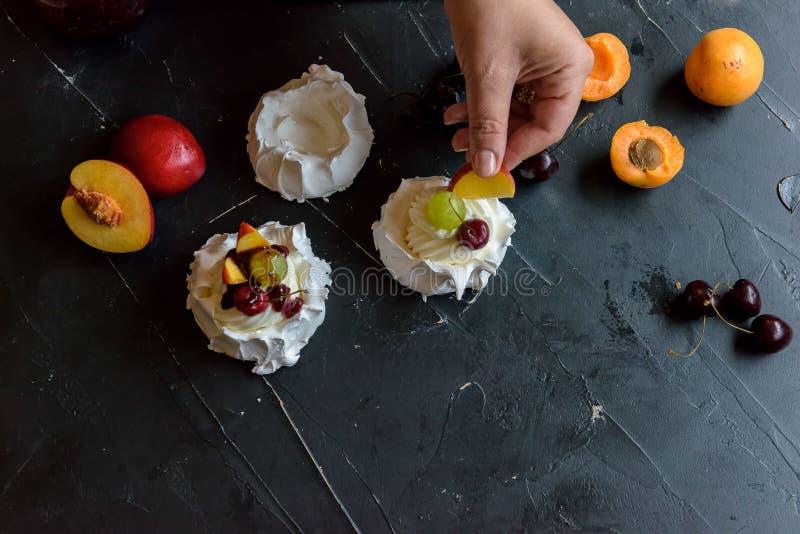 Framställning av en Pavlova efterrätt med frukt och driftstopp royaltyfria bilder