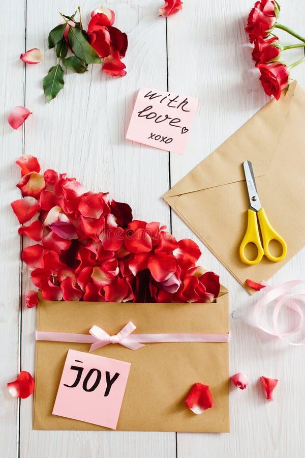 Framställning av förälskelsemeddelandet med kuvertet och rosa kronblad royaltyfri foto