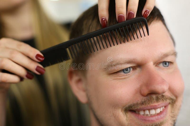 Framställning av frisyr för manklient i frisersalongsalong arkivbild