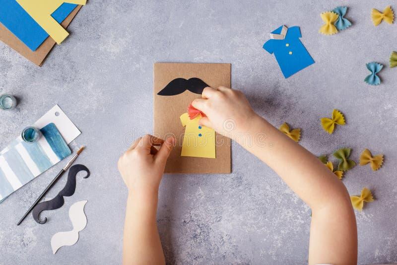 Framställning av hälsningkortet för faderdag Skjorta med fjärilen från pasta Kort från papper moustache Barns konstprojekt royaltyfri fotografi