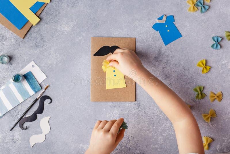 Framställning av hälsningkortet för faderdag Skjorta med fjärilen från pasta Kort från papper moustache Barns konstprojekt royaltyfria foton