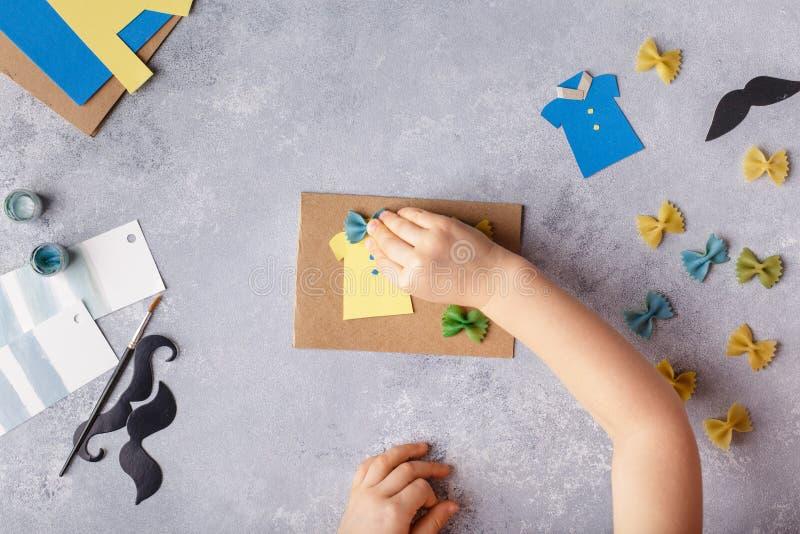 Framställning av hälsningkortet för faderdag Skjorta med fjärilen från pasta Kort från papper moustache Barns konstprojekt arkivbilder