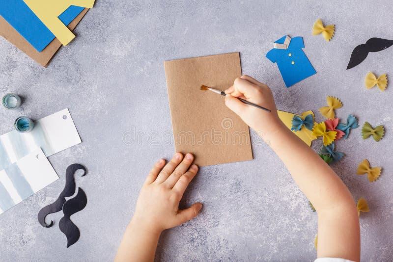 Framställning av hälsningkortet för faderdag Skjorta med fjärilen från pasta Kort från papper moustache Barns konstprojekt arkivfoton