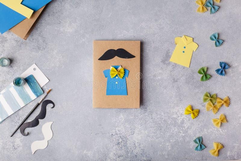 Framställning av hälsningkortet för faderdag Skjorta med fjärilen från pasta Kort från papper moustache Barns konstprojekt royaltyfri foto