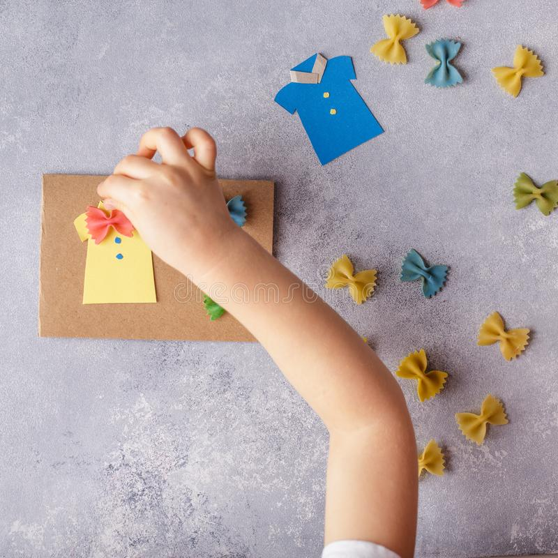 Framställning av hälsningkortet för faderdag Skjorta med fjärilen från pasta Kort från papper moustache Barns konstprojekt fotografering för bildbyråer