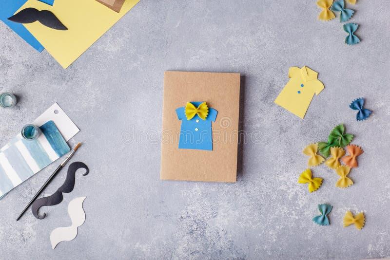 Framställning av hälsningkortet för faderdag Skjorta med fjärilen från pasta Kort från papper moustache Barns konstprojekt royaltyfria bilder