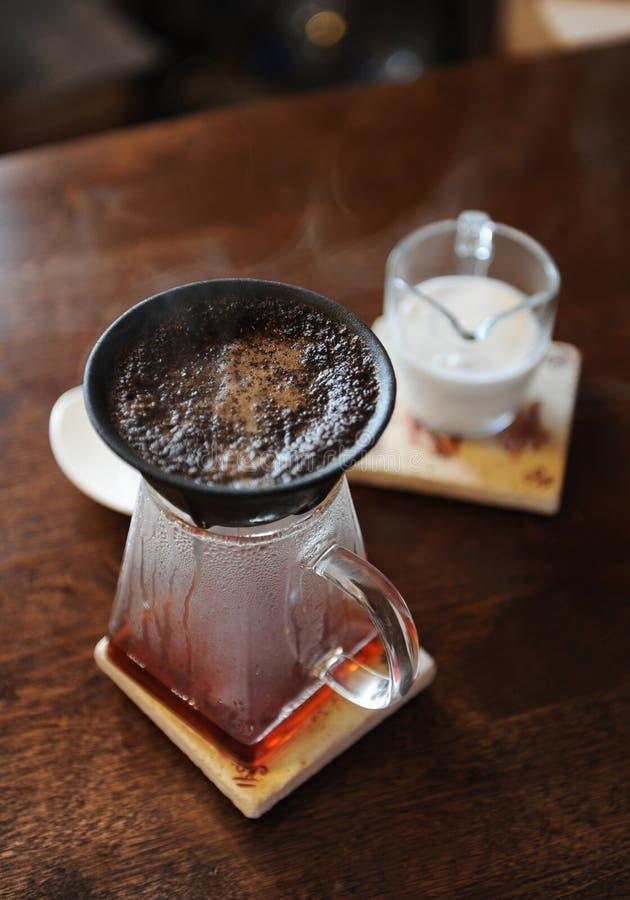 Framställning av kaffe i svart paperless poröst keramiskt porslinfilter på exponeringsglasportiontillbringaren Vit kopp och att m arkivfoto