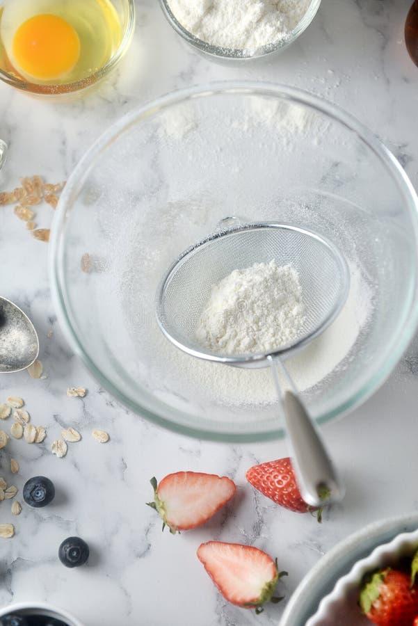 Framställning av pannkakor, kaka, bakning av bagarehänder som siktar mjöl i bunke Begrepp av att laga mat ingredienser och metod  arkivbilder
