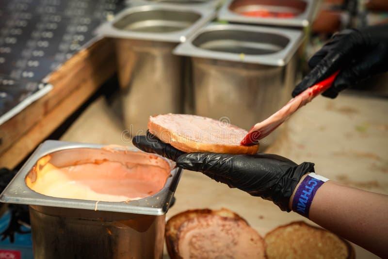 Framställning av sprängkapsel kökshandskar och ostburgare royaltyfri fotografi