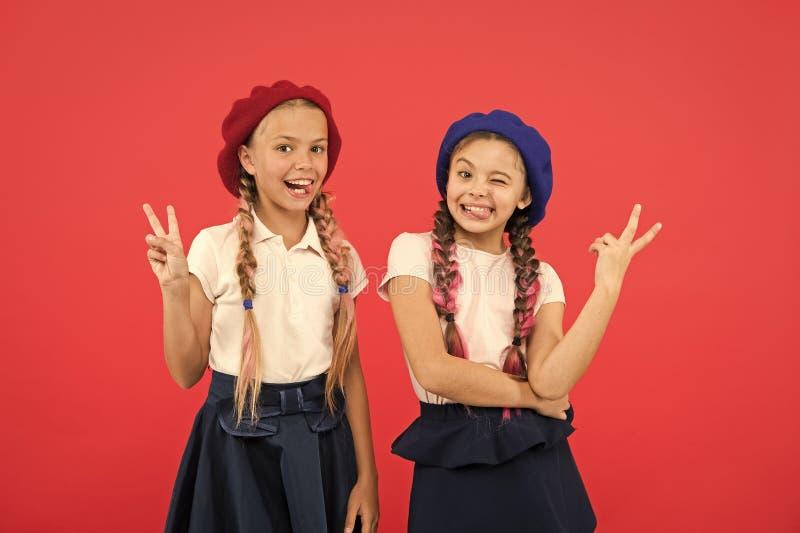 Framst?llning av fredtecken Franska stilflickor Sm? ungar som b?r stilfulla franska basker Gulliga flickor som har den samma fris arkivbilder