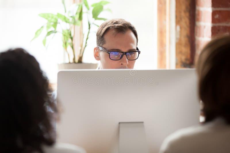 Framstickande direktör som använder datoren som ser bildskärmskärmen royaltyfria foton