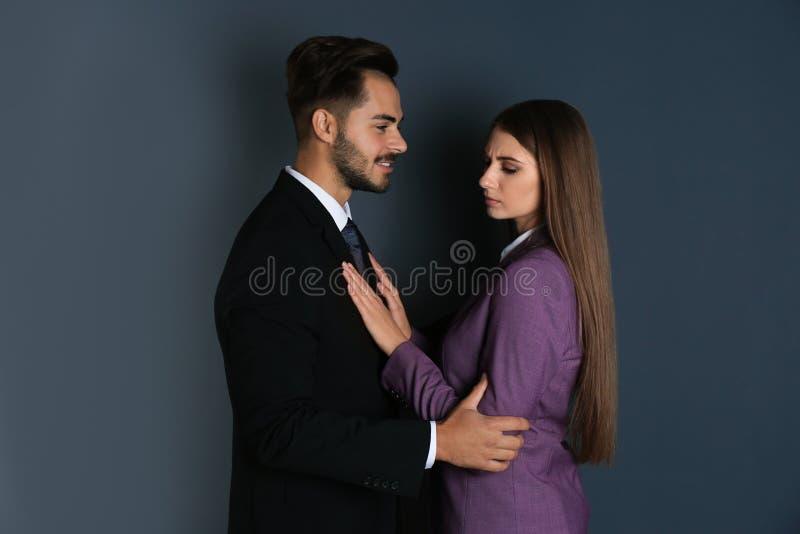 Framstickande som antastar hans kvinnliga sekreterare på mörk bakgrund royaltyfria foton