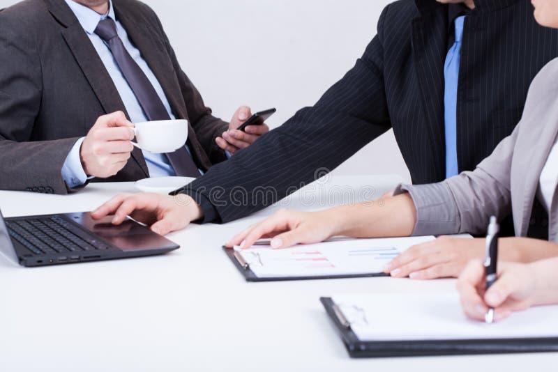 Framstickande som använder telefonen och dricker kaffe arkivfoto