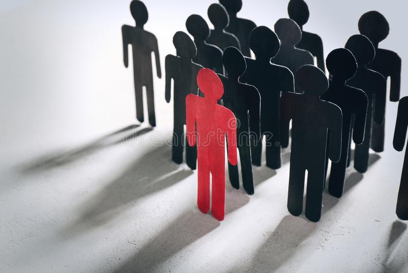 Framstickande vs ledarebegrepp Folkmassa av människadiagram bak röd arkivfoto