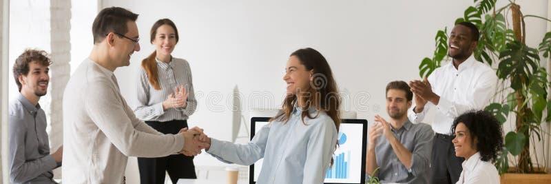 Framstickandehandshaking med kvinnlig anställd för blandat lopp som gratulerar med framgång royaltyfria bilder