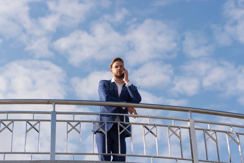 Framstickandesamtal på mobiltelefonen på blå himmel Affärsman med smartphonen Man i formell dräkt på soligt utomhus- Modernt liv  royaltyfri foto