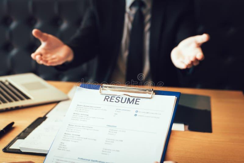Framstickandet argumenterar med en jobbintervjuare om hans arbetshistoria i chefkontoret royaltyfri foto